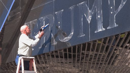 In this Oct. 6, 2014 photo, a worker applies caulk to holes in the facade of the former Trump Plaza casino in Atlantic City N.J. after letters spelling out the casino's name were removed. The casino closed on Sept. 16, 2014, one of four to go out of business in Atlantic City in 2014. After the worst year in the 36-year history of casino gambling in Atlantic City, which saw four of its 12 casinos close, the battered industry bids good riddance to 2014 and hopes for a better roll of the dice in 2015.(AP Photo/Wayne Parry)