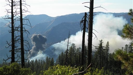 In this photo provided by Donald Talend, smoke rises from a plane crash Tuesday, Oct. 7, 2014, near Chinquapin, Calif. The S-2T air tanker fighting a wildfire near Yosemite National Park in Northern California crashed, but there was no immediate word on the condition of the pilot, who was the only person aboard, officials said. (AP Photo/Donald Talend)