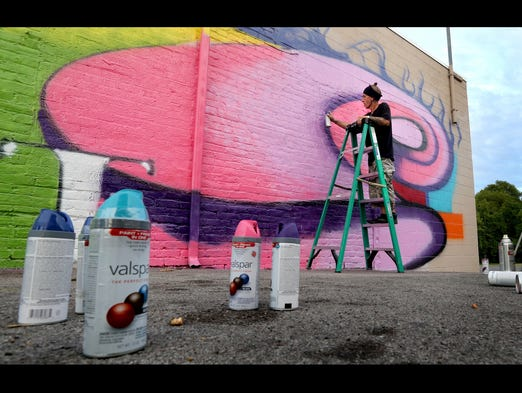 David Hoffman uses spray paint to work on a mural on the side of the building at 517 West Main Street in Murfreesboro, on Friday afternoon August  8, 2014. Some of the spray paint cans used on the mural can be see in the foreground.