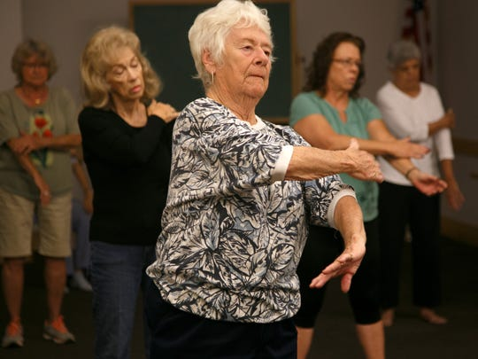 Students in Barbara Mathison's tai chi class work through the movements of the exercise in the community room at the Santa Clara branch of the Washington County Library Saturday, Oct. 24, 2015.