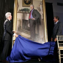 This April, 24, 2006, file photo shows former President Bill Clinton, left, looking up at his portrait after Lawrence M. Small, secretary of the Smithsonian Institution, right, helped him remove the drape at the Smithsonian Castle Building in Washington. A Philadelphia artist says that his museum portrait of former President Clinton contains a shadow reference to Monica Lewinsky's infamous blue dress. Nelson Shanks tells the Philadelphia Daily News that a shadow beside Clinton is a literal reference to the dress and a symbolic nod to the shadow the affair cast on his presidency.