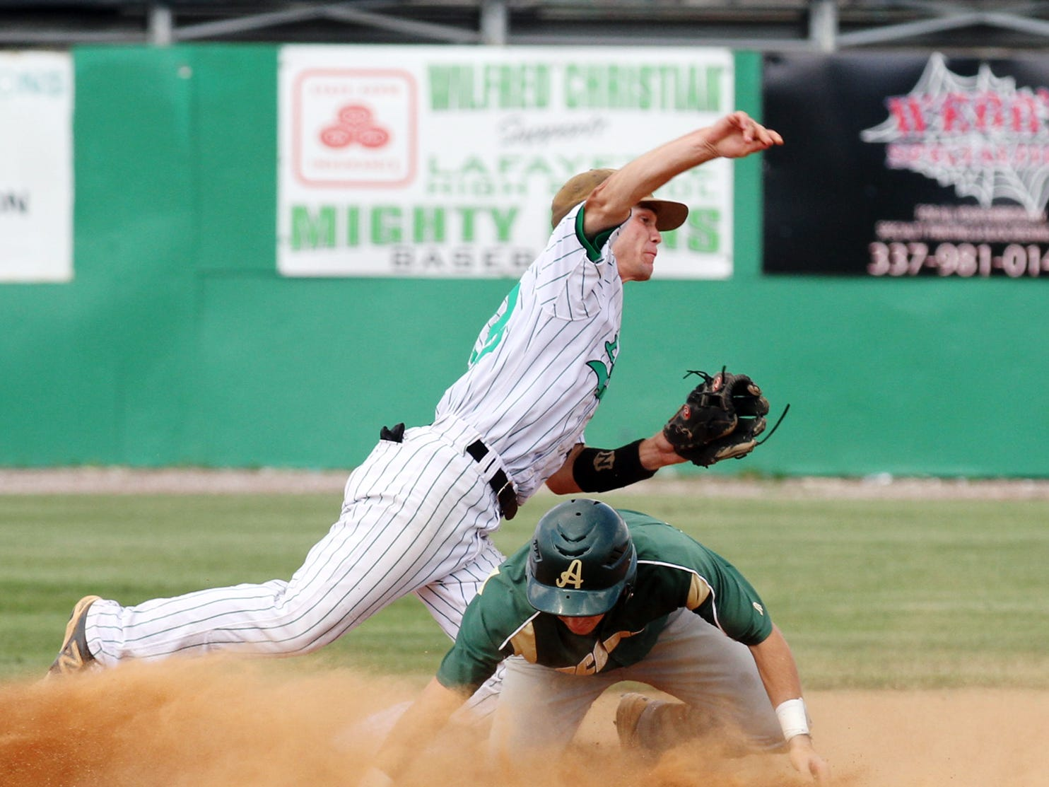 Lafayette High second baseman Owen Thibodeaux (12) attempts to complete a double play after forcing out Acadiana runner Brandon Duhon (8) at second base during Friday's state regional round game one.