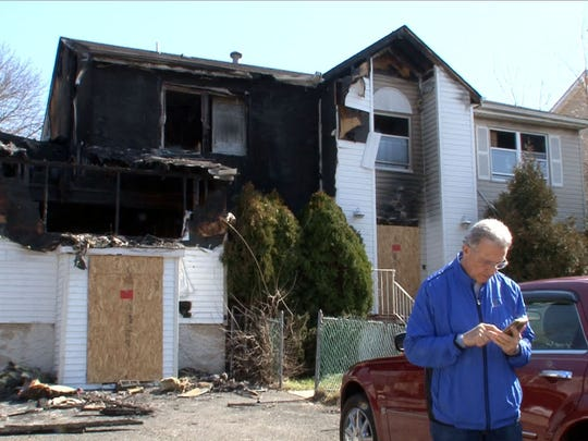 A man who represents the property owner stands outside the single-family home at 825 East End Avenue in Lakewood Tuesday, March 1, 2016, that fire officials report contained 27 beds and had numerous male occupants and was not registered with the state as a dormitory.