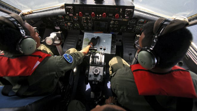 Indonesian Navy pilots Maj. Bambang Edi Saputro, left, and 2nd Lt. Tri Laksono check their map during a search operation for the missing Malaysian Airlines Boeing 777 over the waters bordering Indonesia, Malaysia and Thailand near the Malacca straits on Monday, March 10, 2014.  In an age when people assume that any bit of information is just a click away, the thought that a jetliner could simply disappear over the ocean for more than two days is staggering. (AP Photo/Binsar Bakkara)