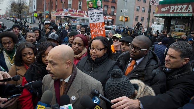 CORRECTS BYLINE  Emerald Garner, daughter of Eric Garner, center, stands with National Action Network members near a makeshift memorial, Monday, Dec. 22, 2014, at the site where New York Police Department officers Rafael Ramos and Wenjian Liu were murdered in the Brooklyn borough of New York. Police say Ismaaiyl Brinsley ambushed the two officers in their patrol car in broad daylight Saturday, fatally shooting them before killing himself inside a subway station. (AP Photo/John Minchillo)