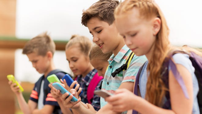 A group of kids sit together while using their smartphones.