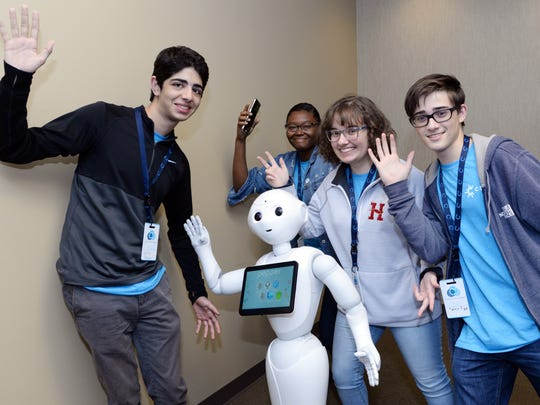 Students from Hartfield Academy share a lighter moment with Pepper, a four-foot tall humanoid robot with a tablet for a chest, at C Spire's C3 coding challenge. The Ridgeland-based technology company wants students to learn more about information technology, computer science principles, robotics and artificial intelligence.