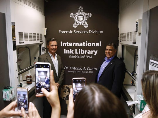 In this June 27, 2019 photo, Vidal Cantu, left, and Arnold Cantu pose for photos in the International Ink Library, which was dedicated in remembrance of their uncle, former U.S. Secret Service chief chemist Antonio Cantu, during a visit to the Secret Service headquarters building in Washington. (AP Photo/Patrick Semansky)