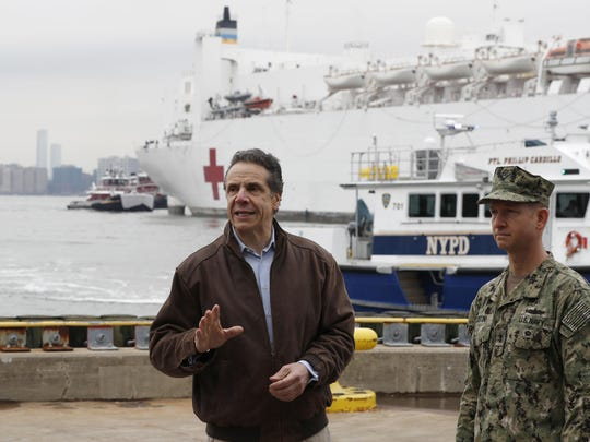 New York Gov. Andrew Cuomo, left, gestures during a brief news conference as he stands beside a Rear Adm. John B. Mustin as the USNS Comfort, a naval hospital ship with a 1,000 bed-capacity, pulls into Pier 90 Monday, March 30, 2020, in New York. The ship will be used to treat New Yorkers who don't have coronavirus as land-based hospitals fill up with and treat those who do. (AP Photo/Kathy Willens)