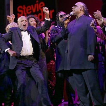 Berry Gordy, founder of Motown, dances while Stevie