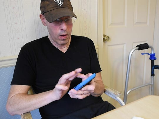 Larry Goldman uses a text-to-speak device, at his home in York Township, while describing his waterboarding experience in the Navy during the 1970s.