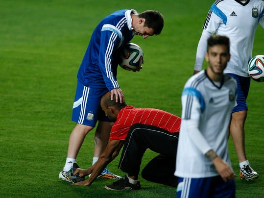 A fan who invaded the pitch shines the cleats of Argentina's Lionel Messi at the end of a training session at Independencia Stadium in Belo Horizonte, Brazil, Wednesday, June 11, 2014. Argentina will play in group F of the Brazil 2014 soccer World Cup. (AP Photo/Victor R. Caivano)