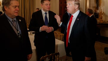 President Donald Trump talks with Tesla and SpaceX CEO Elon Musk, center, and White House chief strategist Steve Bannon during a meeting with business leaders in the State Dining Room of the White House in Washington, Friday, Feb. 3, 2017.