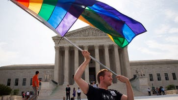 In a June 25, 2015 file photo, John Becker, 30, of Silver Spring, Md., waves a rainbow flag in support of gay marriage outside of the Supreme Court in Washington.