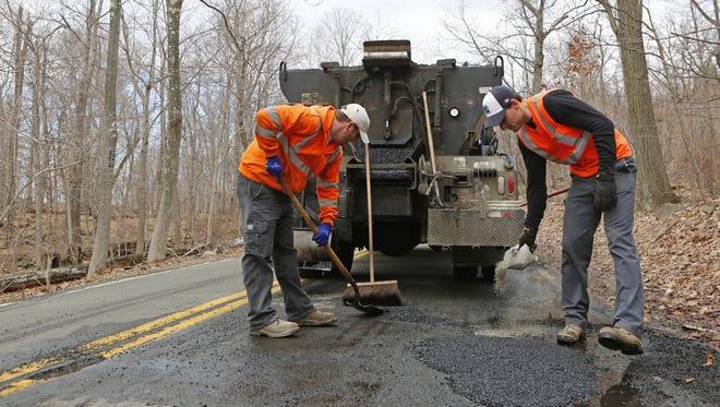 Orangetown Highway Department workers George Garrecht, left, and Bryan Antonutti repair potholes on Schuyler Road on March 20 in Orangetown.