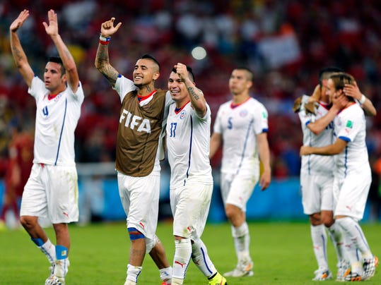 Chile's national team celebrate after their victory over Spain during the group B World Cup soccer match between Spain and Chile at the Maracana Stadium in Rio de Janeiro, Brazil, Wednesday, June 18, 2014. Defending champion Spain was eliminated from the World Cup after losing to Chile 2-0. (AP Photo/Frank Augstein)
