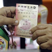 A clerk hands over a Powerball ticket to a customer, Wednesday, Jan. 6, 2016, at a local grocery store in Hialeah, Fla.