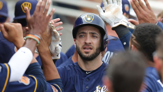 Ryan Braun celebrates with teammates after scoring a run during a spring training game against the Giants.