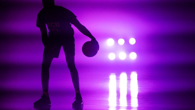 Grand Canyon University men's basketball player Kerwin Smith strikes poses for a videographer in a smoke-filled gym at the school, Wednesday, September 6, 2017, as part of media day.