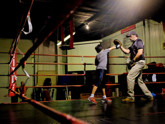 Big Dog Boxing Club trainer Jim Smedley in the ring with a fighter.