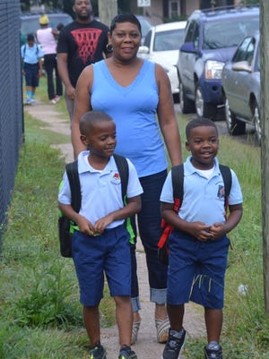 Janis Alfred (center) walks her grandsons, 7-year-old brothers Caleb Alfred (left) and Caden Alfred, to school at Bunkie Elementary Learning Academy Monday.