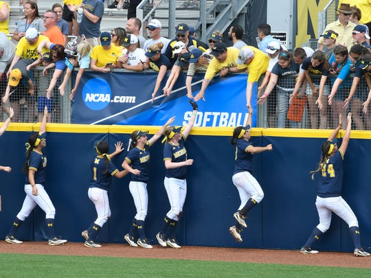 Michigan players circle around Alumni Field with high-fives for fans after their win Sunday over Missouri.
