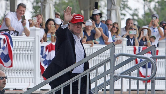 President Donald Trump waves to the crowd as he climbs the stairs to his box where he watched the golf tournament at Trump National Golf Course.