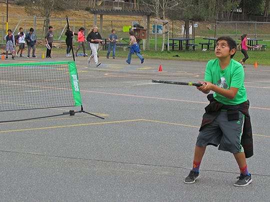 Rafael Ayala, juggles the ball on the racket in one of the skill game areas on the playground.