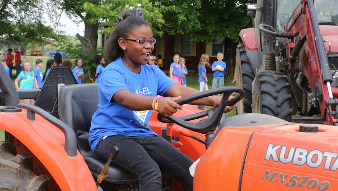 Erma Siegel Elementary School third-grader Kaitlyn Reed sits on a tractor while on a field trip at the MTSU Farm on Thursday.