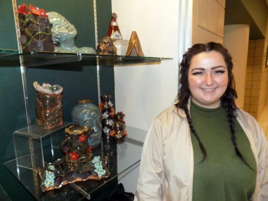 Kat McCarthy, Novi High School senior, with her ceramic collection that won a gold key portfolio award. The collection will now go on to Scholastic competition in New York City.