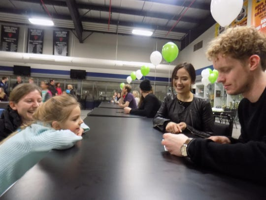 Evan Bates and Madison Chock, world championship bound ice dancers, sign autographs for Sally Tsybulevsky, 4, also a figure skater, as her mother, Oxana Tsybulevsky, looks on at the Novi Ice Arena.