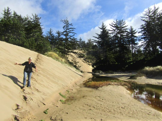 A woman makes her way down dunes to Tahkenitch Creek. A 4.8-mile loop visits the creek and returns through dunes and tree islands to the day-use area.