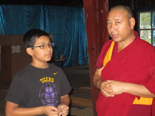 Geshe Thinley speaks to an ESA student before the Tibetan cultural pageant on Thursday, Mar. 26, 2015.