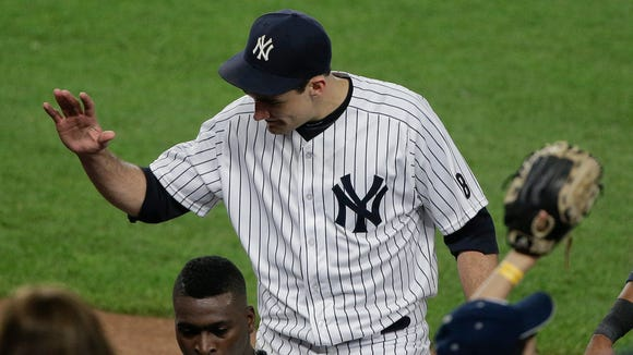 New York Yankees pitcher Nathan Eovaldi is greeted by teammates as he walks off the field at the end of the top of the sixth inning of a baseball game against the Toronto Blue Jays on Tuesday, May 24, 2016, in New York.