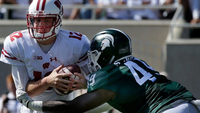 Sep 24, 2016; East Lansing, MI, USA;   Wisconsin quarterback Alex Hornibrook (12) eludes a sack by Michigan State linebacker Shane Jones (49) during the third quarter of their game at Spartan Stadium. Mandatory Credit: Mark Hoffman/Milwaukee Journal Sentinel via USA TODAY Sports
