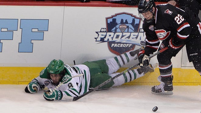 University of North Dakota forward Nick Schmaltz (8) falls to the ice while battling St. Cloud State forward Jonny Brodzinski for the puck during the second period of the NCHC Frozen Faceoff game on March 20, 2015, at the Target Center in Minneapolis.