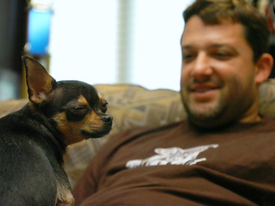 Tony Stewart hangs out on his couch with his chihuahua nicknamed, Poo, at his Columbus, Ind. home.