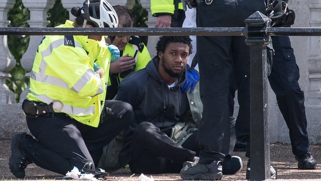 A man is detained by police near Buckingham Palace on Wednesday in London. The Changing of the Guard ceremony has been canceled today so police officers can be redeployed following an increase in the national security level after the terrorist attack in Manchester.