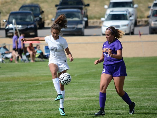Piedra Vista's Alysa Acosta, left, moves the ball in