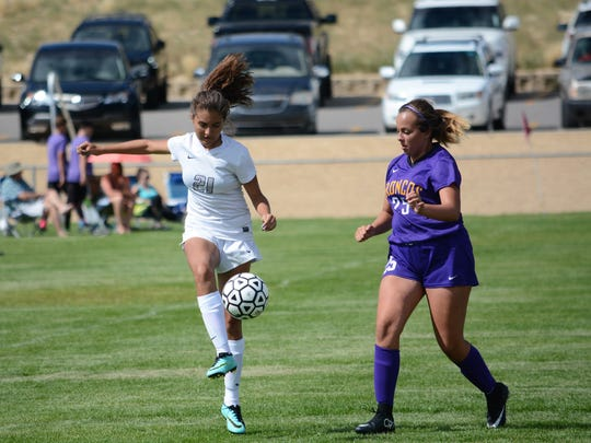Piedra Vista's Alysa Acosta, left, moves the ball in the first half of Tuesday's match against Kirtland Central.