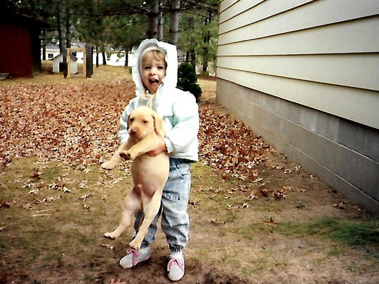 Shaynee Traska as a little girl growing up in Gladwin with her first dog, Vern.