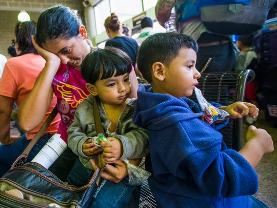 Seydi Maricela Sequeira Alvarenga, 23, and her children, Olvin (left) and Oliver, wait Monday at the Greyhound bus station in Phoenix. Officials say the family attempted to illegally cross into the U.S. outside McAllen, Texas.