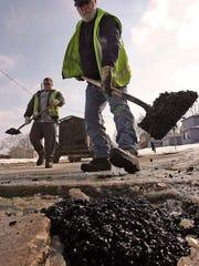 Forest Sanders and Mike Houseman Jr. repairing potholes