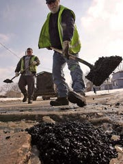 A Des Moines city worker shovels hot asphalt into a pothole on Southeast Third Street on the south side of Des Moines.