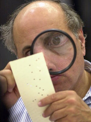 In this Nov. 24, 2000, file photo, Broward County, Fla., canvassing board member Judge Robert Rosenberg uses a magnifying glass to examine a disputed ballot at the Broward County Courthouse in Fort Lauderdale, Fla. Examining sources to find accurate information is a crucial step to ensuring voters are informed.