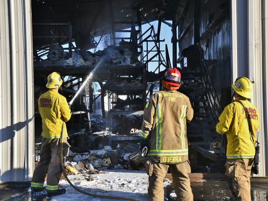 Firefighters continue to monitor a building at Paul