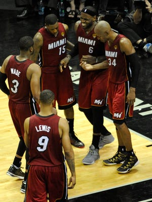 Heat forward LeBron James is helped off the court by teammates with cramps during Game 1 of the Finals.