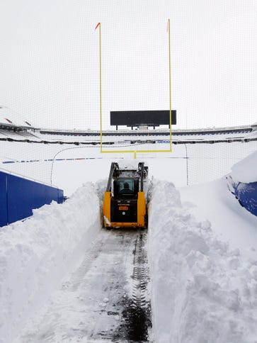 After a major snow storm a grounds crew worker begins