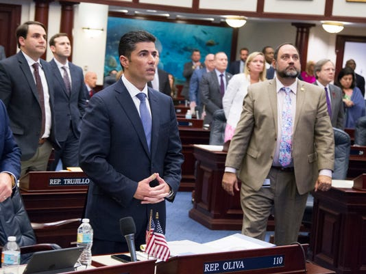 Florida House bill sponsor Rep. Jose Oliva, center, (R- Hialeah), watches the vote board at the Florida Capital in Tallahassee, Fla., Wednesday March 7, 2018. The Florida House has passed a school safety bill that includes new restrictions on rifle sales and a program to arm some teachers. The House voted 67-50 Wednesday on a bill that's a response to the Feb. 14 shooting at a high school that killed 17 people. (AP Photo/Mark Wallheiser)