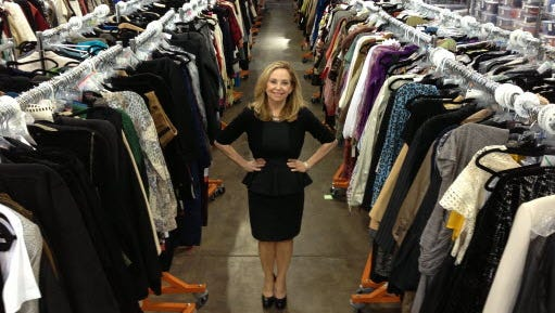 Julie Wainwright, founder of The RealReal, stands amid a sea of high-end consignment goods in her San Francisco warehouse.